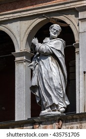Medieval statue of Saint Peter the Martyr with a hatchet in his head decorating the facade of the Cremona Cathedral.