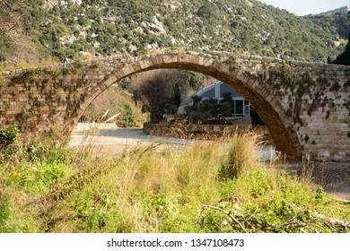 A medieval stone bridge built by Sultan Makluk archs over the Nahr al Kalb dog river near Beirut, Lebanon, Middle East.