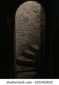 Medieval stone spiral staircase, steps going up to ground floor. Medieval dungeon. Stone steps framed by arched doorway. Going down the basement of a castle.
