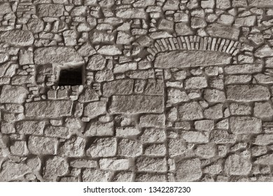 Medieval stone wall of the fortress with a small barred window