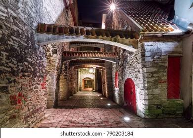 Medieval street St. Catherine's Passage or Katariina kaik, half-hidden walkway in Old Town at night, Tallinn, Estonia