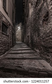 Medieval street that goes up narrow towards Bergamo Alta in the night. Vertical image of nocturnal cityscape.