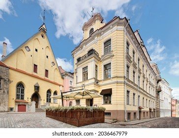 Medieval Tallinn, panoramic image of old town. Ancient houses on cobbled street in medieval center. Wooden terrasse of outdoor cafe or restaurant. Daylight, blue sky with cumulous clouds.