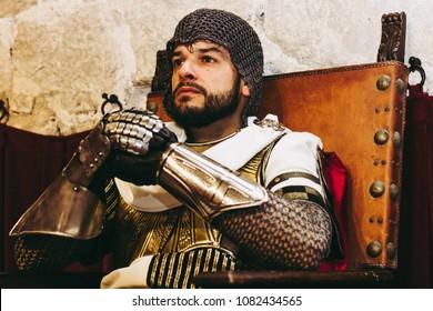 Medieval templar soldier sitting on a throne.