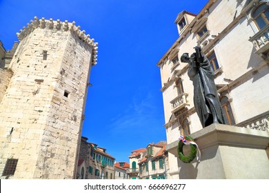 Medieval tower and old statue in sunny square from the old town of Split, Croatia