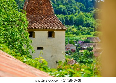 Medieval tower with windows shaped like eyes and mouth, in Biertan, Romania. Old building resembling a human face, partly hidden behind a tree. Original architecture in Transylvania - tourism concept.