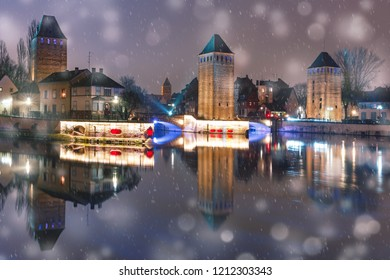 Medieval towers and bridges with mirror reflections in Petite France in the snowy night, Strasbourg, Alsace, France