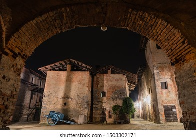 Medieval town at night with horse cart, old houses, ivy and lights