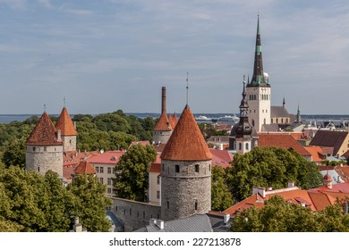 Medieval town rooftop view. Tallinn churches and towers steeples. Beautiful aerial view of european medieval town. Tiled roofs and old towers of Tallinn's medieval town.