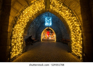 Medieval town wall arches decorated with Christmas lights during holiday season. Visby. Gotland. Sweden.