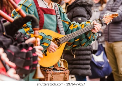Medieval troubadour playing an antique guitar.