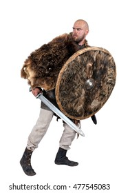 Medieval Viking with a sword and a round shield in bearskin. Isolated on white