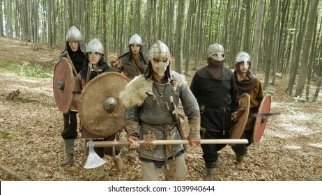 Medieval Vikings running in the forest to fight in a battle. Vikings clad in chain mail, with shields, swords, spears, axes and helmets on their heads. Beech forest. Medieval Reenactment.