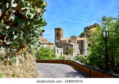 The medieval village of Savoca in Sicily, movie location of Godfather, a cobblestone footpath in front, prickly pear plant on the left, a nostalgic street lamp on the right, a sunny day in summer