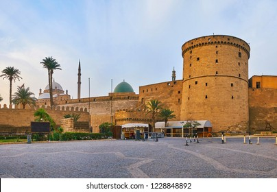 The medieval walls of Saladin Citadel hide its main landmarks - the Alabaster Mosque with tall minarets and Al-Nasir Muhammad Mosque with mosaic green dome, Cairo, Egypt.