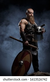 Medieval warrior berserk Viking with axes attacks enemy. Concept historical photo of Scandinavian god in armour and helmet with horns