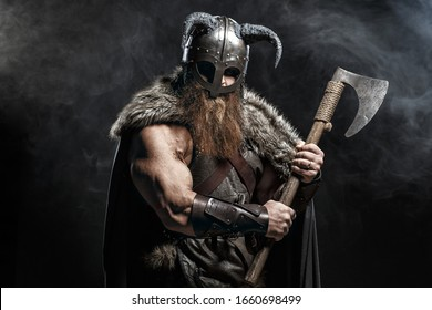 Medieval warrior berserk Viking with axes attacks enemy. Concept historical photo of Scandinavian god in armor and helmet with horns