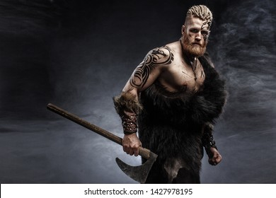 Medieval warrior berserk Viking with tattoo with axes attacks enemy. Concept historical photo