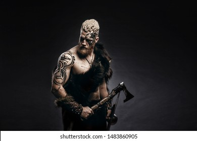 Medieval warrior berserk Viking with tattoo on skin, red beard and braids in hair with axe and shield attacks enemy. Concept historical photo