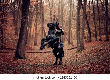 Medieval Warrior Man on a black horse standing on two legs. Reconstruction of a medieval war scene in the woods, in autumn.