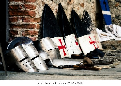 Medieval weapons, shields and helmets from the crusade age on a castle floor during an historical reenactment