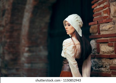 Medieval Woman in Historical Costume Wearing Corset Dress and Bonnet. Beautiful peasant girl wearing Halloween outfit