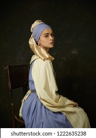 Medieval Woman in Historical Costume Wearing Corset Dress and Bonnet. Beautiful peasant girl wearing thrush costume