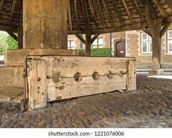 Medieval wooden stocks at the Old Butter Cross, Oakham, Rutland, England, UK.