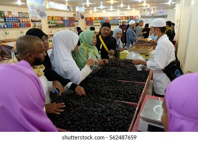 MEDINA, SAUDI ARABIA - 1 DECEMBER 2016 : Muslim pilgrims from Malaysia and Indonesia buying dates fruit in Madinah dates farm.