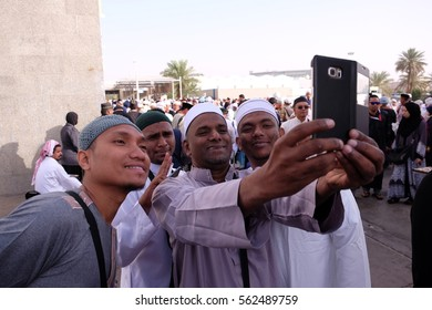 MEDINA, SAUDI ARABIA - 1 DECEMBER 2016 : Group of mualaf (muslim convert) taking selfie during their pilgrimage trip in Medinah.