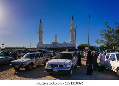 Medina, Saudi Arabia, 2018 Dec 8: Crowd of tourists doing their activities outside Quba Mosque. Focus at center. Others in gradient blur. Blue sky background with bright light at left.