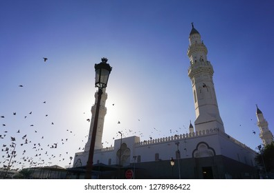 Medina, Saudi Arabia, 2018 Dec 8: Image of 3 of minarets at Quba Mosque with beautiful cloudless blue sky background. Focus at highest tower. Others in gradient blur. Strong backlight on left.