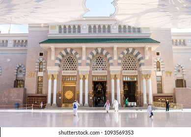 MEDINA, SAUDI ARABIA - APRIL 28 2018: Prayers walking in the entrance gate of Al-Masjid Al-Nabawi or Prophet Muhammed Mosque, the most beautiful mosque in the world, located in City of Medina