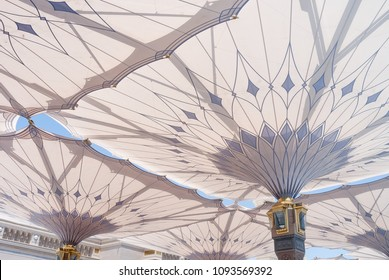 MEDINA, SAUDI ARABIA - APRIL 28 2018: These Umbrella construction on the square of Al-Masjid An-Nabawi or Prophet Muhammed Mosque are protecting people from sun at daytime and work as lights at night