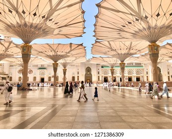 Medina, Saudi Arabia - March 26, 2018: Exterior view of Nabawi  Mosque building in Medina (Madinah) and unidentified pilgrims with selective focus and crop fragment