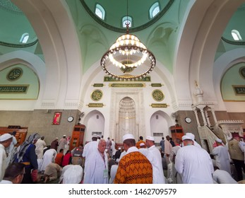 Medina, Saudi Arabia - March 28, 2018 : Beautiful view of interior Quba Mosque and unidentified muslim praying inside the mosque.  Selective focus