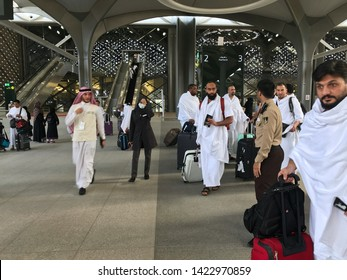 MEDINA, SAUDI ARABIA - MAY 27, 2019 :  a group of men in white ihram clothes ready to embark train coaches at HSR Madinah station in Medina, Saudi Arabia.
