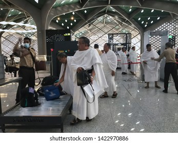 MEDINA, SAUDI ARABIA - MAY 27, 2019 : Unidentified Muslim pilgrims in white ihram clothes pass through a security check at HSR Madinah station in Medina, Saudi Arabia.