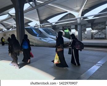 MEDINA, SAUDI ARABIA - MAY 27, 2019 :  a group of women in black abayas ready to embark train coaches at HSR Madinah station in Medina, Saudi Arabia.