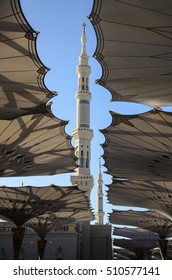 MEDINA, SAUDI ARABIA - NOVEMBER 6: A minaret / tower through an opening among the giant umbrellas at the Prophet Mosque (Masjid Nabawi) on November 6, 2016. The mosque was founded by Prophet Muhammad.