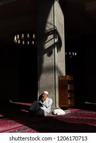 MEDINA, SAUDI ARABIA-CIRCA 2016: Unidentified old Muslim bearded man reads Koran inside Quba mosque in Madinah, Kingdom Saudi Arabia.
