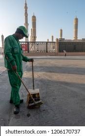 MEDINA, SAUDI ARABIA-CIRCA 2016: Unidentified Asian origin man cleans the road outside Nabawi mosque in Al Madinah, Kingdom of Saudi Arabia.