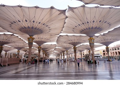 MEDINA, SAUDI ARABIA-CIRCA MAY 2015: Pilgrims walk underneath giant canopies in Nabawi Mosque on MAY, 2015 in Medina, Saudi Arabia .The Nabawi mosque is the second holiest mosque in Islam.
