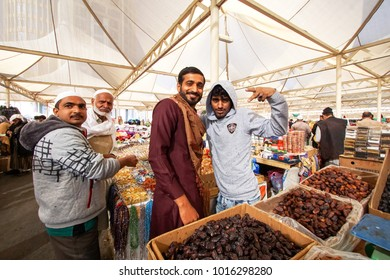 MEDINA, SAUDI ARABIA-DEC 22, 2017: Unidentified Muslim shop keeper selling various types of dates and other dried food.