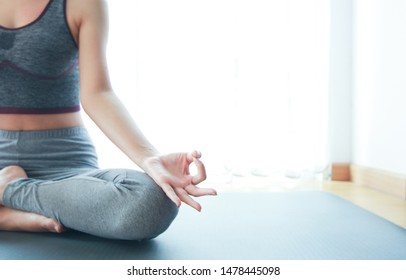 Meditate hands of beautiful Asian young woman practicing yoga indoor doing meditation. Healthcare, lifestyle concept.National Physical Fitness and  Sports Month.National Yoga Awareness Month