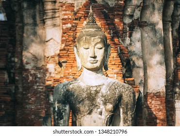 Meditating Buddha sculpture portrait in the middle day sun light rays on the old city brick wall background in ancient Ayutthaya, Thailand.