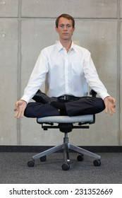 meditating caucasian businessman in lotus pose on office chair