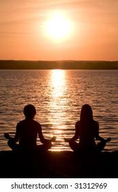 Meditating couple sitting in pose of lotus during wonderful sunset