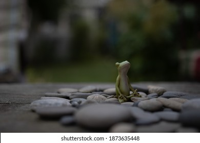 A meditating frog statue in the middle of a stack of soft and rounded stones.