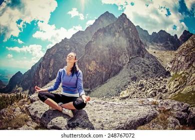 Meditating girl in High Tatras mountains, Slovakia. Yoga in nature